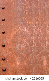 Rusty metal for background.  Six rusted rivets down the left hand side.
