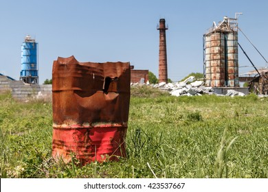 Rusty metal barrel without cover in the territory of plant