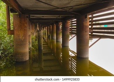 Rusty metal columns of the base of a wooden pier in the water of a river in summer. View under the pier.
