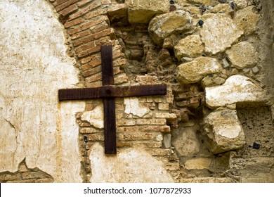 Rusty Metal Cross hanging on a rustic stone wall