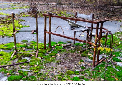Rusty metal frame of table and chair in schoolyard in dead abandoned ghost town of Pripyat in Chernobyl NPP alienation zone, Ukraine