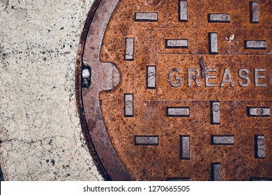 Rusty metal grease trap cover on concrete floor.