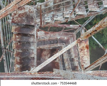 Rusty metal or iron stairs in park or forest, observatory tower with many floors. Industrial view of urban construction. High watch tower. Brown rust and dirty steps and railings.