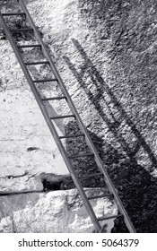 Rusty metal ladder on a stone wall in an old abandoned stone quarry.