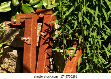 Rusty metal pieces leaning against stone wall overgrowing by lush green plants on a summer day.