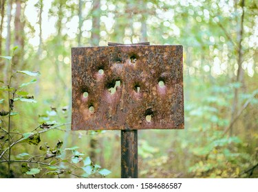 A rusty metal plate shot through in several places is part of an old military gunshot target in the woods
