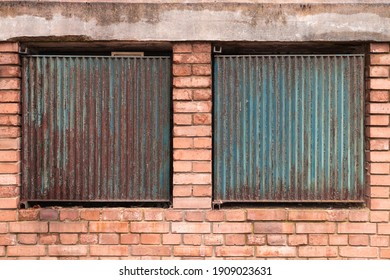 Rusty metal plates fixed on two windows in a brick wall