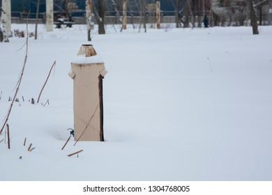 Rusty metal poles in the Park, public garden. Winter weather, snow.