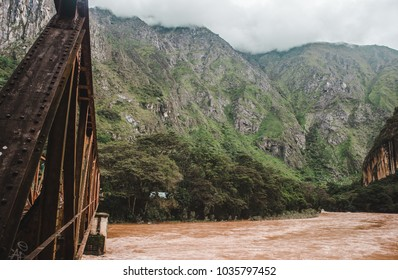 Rusty metal railway bridge over the Urubamba River in the Andes, which carries the train to Machu Picchu in Peru