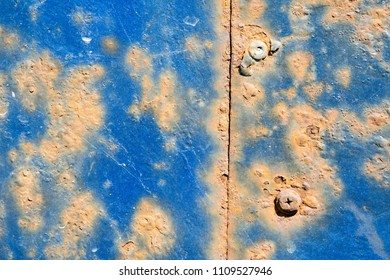 Rusty metal. Screw heads. The old wall. Diffused paint. Blue color.