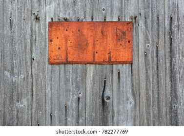 Rusty metal sign on wooden wall, copy space.