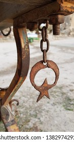 Rusty metal star shaped detail closeup. Turkish symbols star and moon hanging on rough rusty chain under rural wood wagon. Rusty metal texture. Old Turkish star and moon decorations. Vintage objects