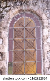 Rusty metal structure of window of old stone building.