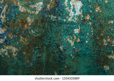 Rusty metal wall, old iron sheet, covered with rust with multi-colored paint. Trace of remnant of old paint in large deep crack on texture of surface rusty metal. Background texture old paint on metal