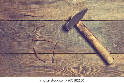 Rusty nails with a hammer on a wooden surface. Top view.