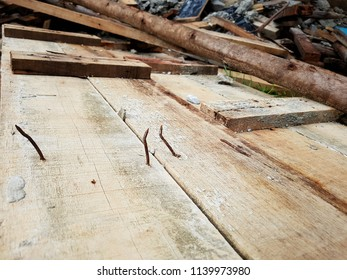 The rusty nails on the hard wood in the construction site, it's very dangerous and not safety. Safety management issue, the workers will get hurt easily step over the rusty nails.