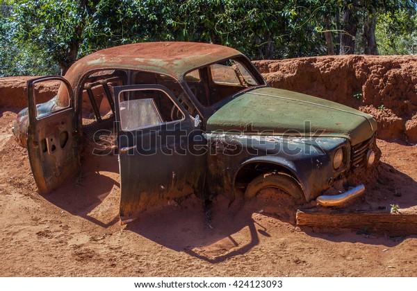 Rusty old abandoned car stuck in the mud in the afternoon sun.