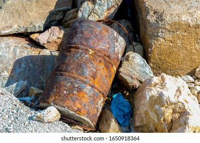 Rusty old barrel on the rocks by the seashore polluting the enviroment. Stock Image.