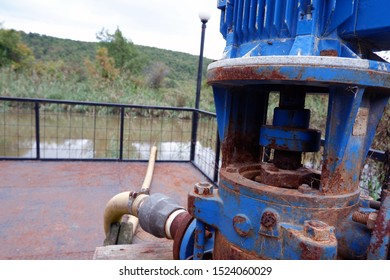 Rusty, old and blue colored water pump. The hose connected to water pump enters the river.