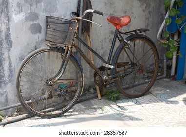 A rusty old Chinese bicycle in an alley