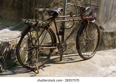 A rusty old Chinese bicycle by the side of the road