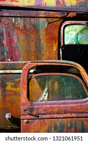 A Rusty Old Door Leaning Against an Old truck