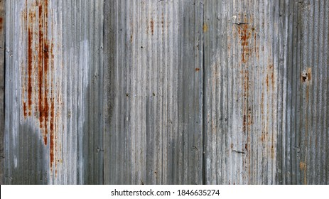 Rusty old galvanized fence. The background and texture of the broken and dirty silver wavy metal lines fill the frame rate. wallpaper for design work with copy space. select focus