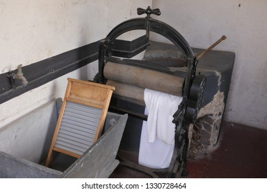 A rusty old hand operated cloth washing and dring press machine.