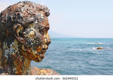 Rusty old head of the statue on the beach. Illustration to an article about the dangers of antiquity or sunburn and skin diseases