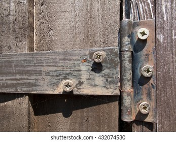 Rusty old iron hinge on timber garden shed door