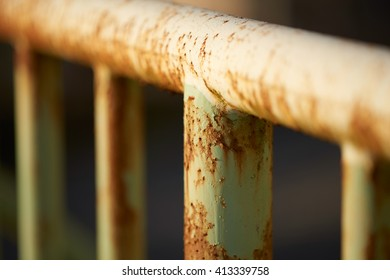 Rusty old poles on an iron fence with a very shallow depth of field.