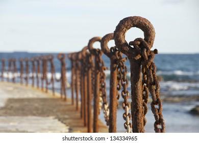 Rusty old post and chain bollards, Newcastle Beach, NSW, Australia