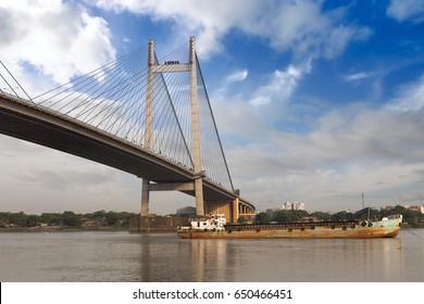 Rusty old ship anchored near the Vidyasagar Setu bridge on river Hooghly. Vidyasagar bridge is the longest cable stayed bridge in India.