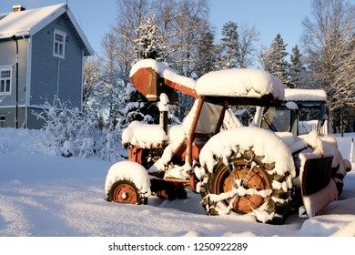 Rusty old tractors left in the snow in an abandoned neighborhood