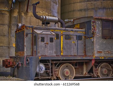 Rusty Old Train Engine sits idle on some tracks near some concrete silos