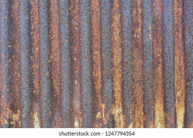 Rusty on old corrugated metal roof sheet. Can used for abstract background. Vintage surface background.
