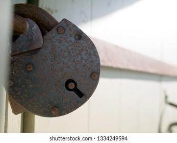 Rusty padlock against locked up wooden  door