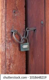 Rusty padlock on old brown wooden door