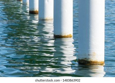 Rusty pier posts in salt sea water. White columns diagonal. Pillars mount for bridge. Sunny weather.