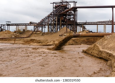 rusty pipe on the river bank, from which sewage flows, dirty sand slurry, and stationary rusty gravitational sand and gravel separator on the background