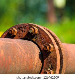 Rusty Pipeline Connection In Front of Green Background