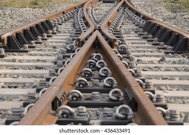 Rusty railroad tracks with rivets as background featuring the switching point, focal point at the upper center of the image