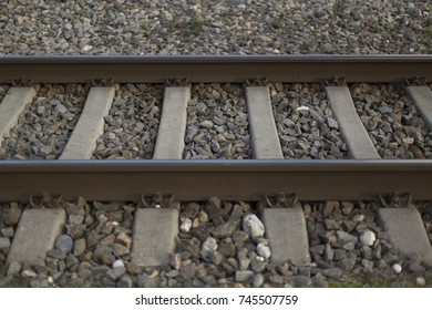Rusty rails and gray crushed stone closeup background