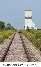 Rusty railway tracks lead to the prairie horizon and a distant white grain elevator
