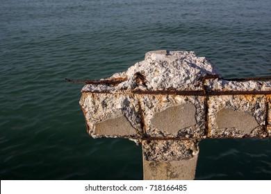 Rusty rebar with old concrete bridge near the sea, corrosion in salt air.