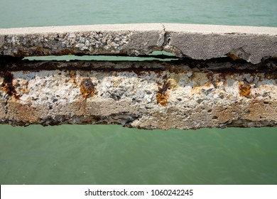 Rusty rebar in the old concrete at harbor bridge, corrosion in salt air with green sea background.