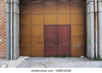 Rusty red door entrance of an abandoned factory with square yellow walls
