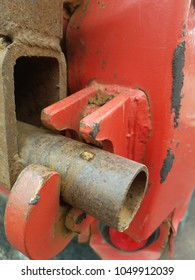 rusty red tailgate latch on a dump truck