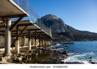 Rusty reinforced concrete columns and concrete platform on the south sea coast near the mountain