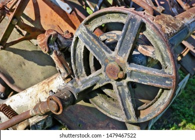 Rusty  retro vintage  small  tractor  gears and wheels background. The metal equipment is made more than hundred years ago. Mass production.